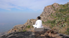 Man sits in meditation in the mountains - stock footage