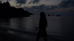 Stock Video Footage of Silhouette of a Girl with Long Hair in a Short Dress Walks on the Beach at