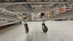Shopping cart parked in busy aisle being load by unseen couple hyperlapse - stock footage