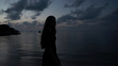 Silhouette of a Girl with Long Hair in a Short Dress Walks on the Beach at - stock footage