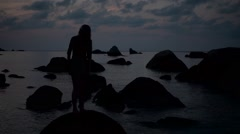 Silhouette of a Girl in a Short Dress Sitanding on a Rock and Waved Her Hair on - stock footage
