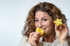 Healthy young woman enjoying a Carambola - stock photo