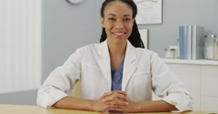 Black woman doctor sitting at desk smiling Stock Footage