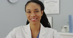 African woman doctor sitting at desk smiling Stock Footage