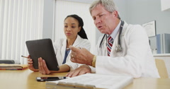 Black and Caucasian doctors working on a tablet in the office - stock footage