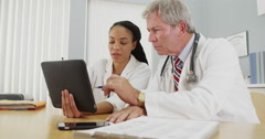 Successfull doctors working on a tablet in the office - stock footage