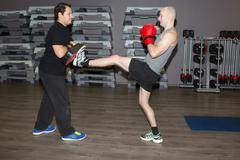 Men doing physical exercises and practicing boxing at fitness center Kuvituskuvat