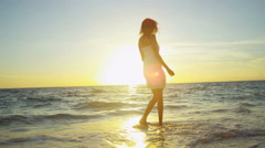 Happy young Latin American girl barefoot on sunset tropical beach - stock footage