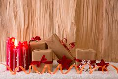Christmas gifts and red Advent candle. - stock photo