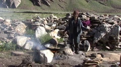 Farmer roasting barley over fire. Stock Footage