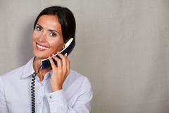 Stock Photo of Toothy smile lady speaking on the phone in button down shirt while looking at