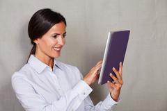 Stock Photo of Long hair lady in formal clothing holding and using tablet with toothy smile