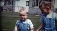 1957: Baby brothers playing modest backyard together matching blue overalls.  - stock footage