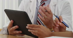Closeup of two doctors using a tablet in the office - stock footage