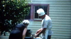 1957: Mother in black giving cook son hard time grilling outdoor chef hat. Stock Footage