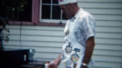 1957: Man chef hat cooking barbeque outdoor apron clean grill closeup. DENVER, Stock Footage