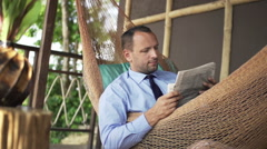 Young businessman reading newspaper on hammock on terrace Stock Footage