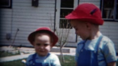 1957: Boy brothers red Swiss alpine hats blue overalls backyard play fun times. Stock Footage