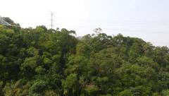 Transmission tower in forest on mountainside, aerial slide view, foggy horizon - stock footage