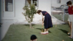 1957: Girl play croquet games backyard annoying practice swing style. DENVER, - stock footage