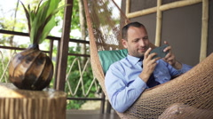 Happy businessman playing game on smartphone on hammock, super slow motion 240fp Stock Footage