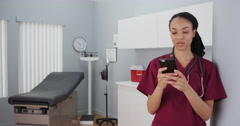 Black woman nurse texting on smartphone Stock Footage