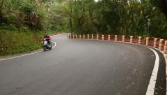 Empty road meanders throughout mountainside, alone motorbike ride towards Stock Footage
