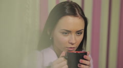 close up of young woman enjoying coffee with foreground flare - stock footage