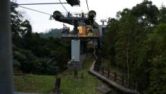 Cable car gondola pass pole before middle station, dusk woodland mountain Stock Footage