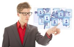 Young business man selecting virtual worldwide friends isolated on white back Stock Photos