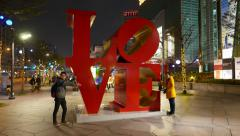 LOVE word sculpture from big red characters, tourists take pictures against art Stock Footage