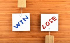 Win lose two paper notes in different directions on wood - stock photo