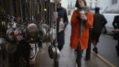 Couple stroll past  a shop selling pocket watches on Portobello Road - 60fps Stock Footage