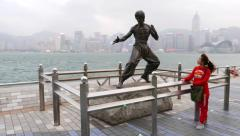 Tourist girl pose with Bruce Lee statue, Avenue Of The Stars, HK Stock Footage