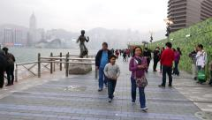 Tourists take picture against Bruce Lee statue, Avenue Of The Stars, Hong Kong Stock Footage
