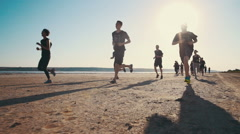 Group of people running on the beach in sunset, slow motion Stock Footage