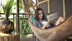 Young businesswoman reading newspaper on hammock on terrace Stock Footage