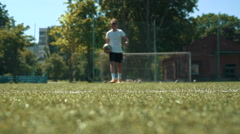 Young man going on the football field and putting ball on the grass - stock footage