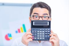 Young businessman upholding a calculator Kuvituskuvat