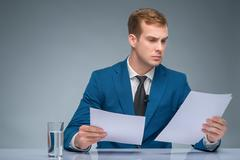 Serious-looking newscaster reading his papers - stock photo