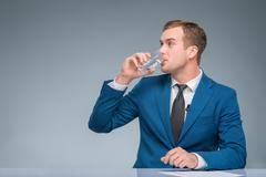 Newsman drinking water at his desk - stock photo