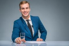 Smiling newsman holding a glass of water Stock Photos
