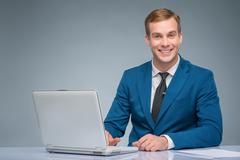 Smiling newsman working with his laptop - stock photo