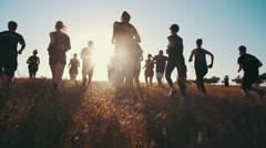 Group of people running on a field in sunset, slow motion Stock Footage