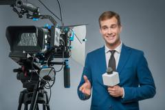 Smiling newsman with a microphone Stock Photos