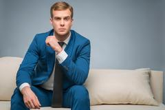 Handsome man sitting on the sofa Stock Photos