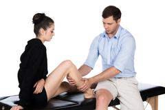 Physiotherapist massaging patient - stock photo