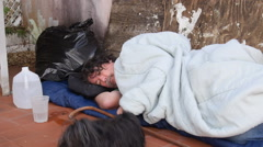 homeless jobless sleeping on the floor playing with dog - stock footage