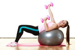 woman with gym ball and dumb bells isolated - stock photo