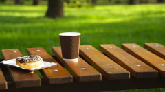 Cup of latte and muffin on a park bench Stock Footage